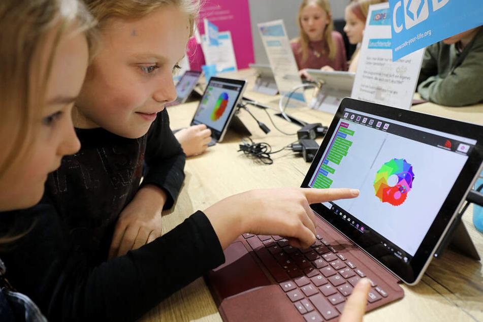 Kinder betrachten auf der Didacta in Köln einen Laptop.