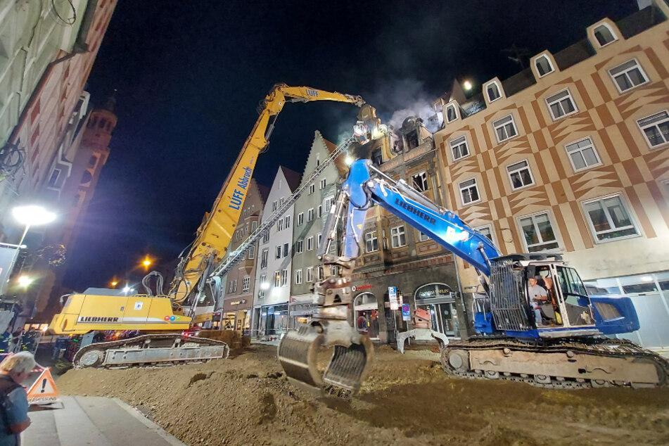 Bagger stehen vor dem denkmalgeschützten Haus in Augsburg, aus dem es noch qualmt. Das Feuer hat das historische Gebäude schwer beschädigt, es musste weitestgehend abgetragen werden.