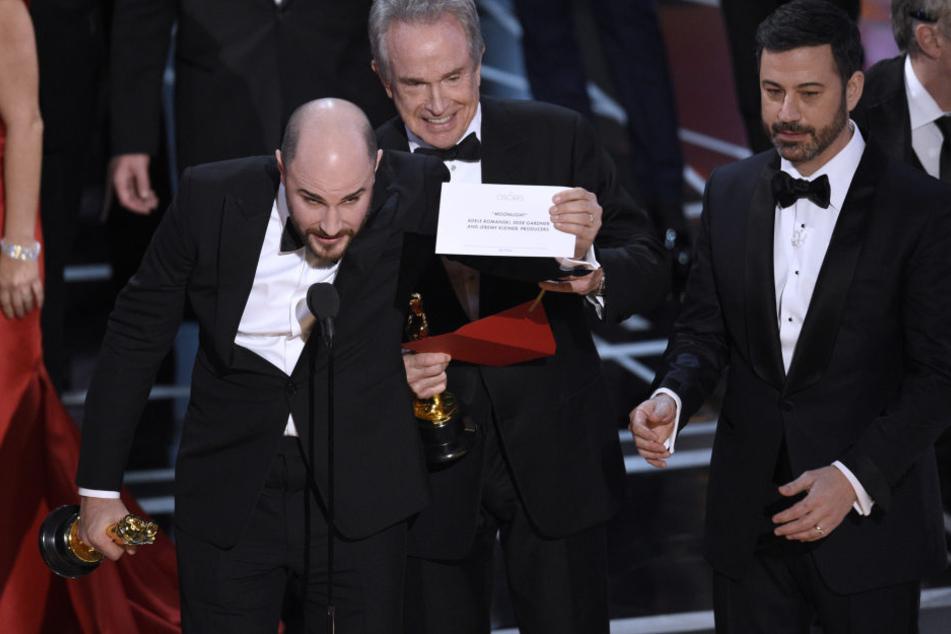 """Nach einer versehentlich falschen Bekanntgabe des besten Films zeigt Jordan Horowitz (l), Produzent des Films """"La La Land"""", den Umschlag mit dem wirklichen Gewinner des Awards für den besten Film."""