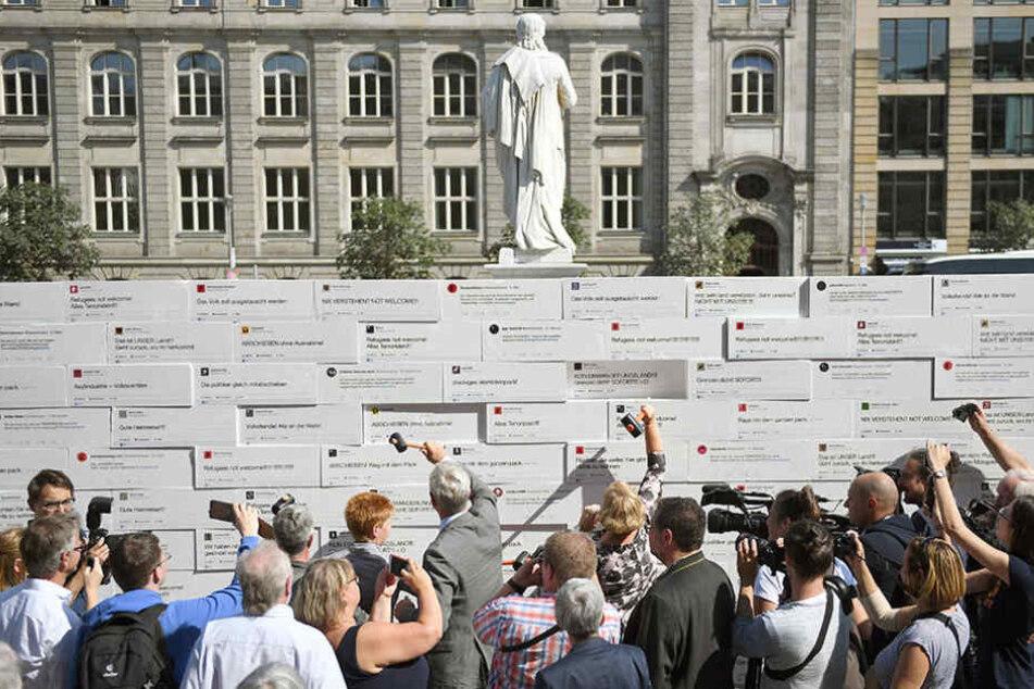 Politiker, Aktivisten und Passanten schlagen auf dem Gendarmenmarkt auf eine Mauer mit Steinen aus Styropor ein.
