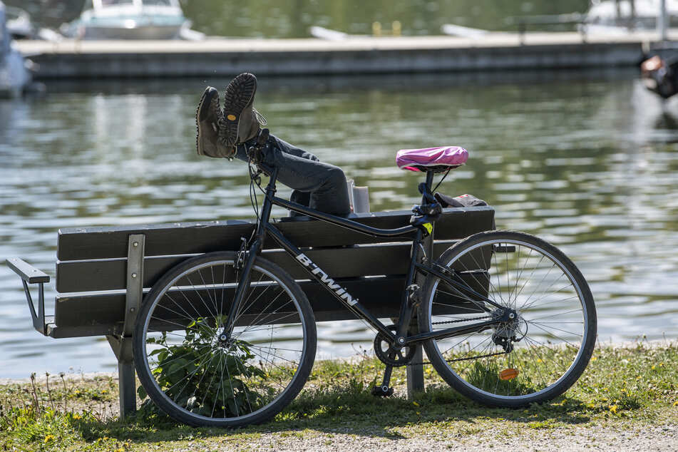 Ein Radfahrer ruht sich an einem sonnigen Tag neben einem Kanal am Djurgarden in Stockholm auf einer Bank aus. Bald kann er wieder richtig weit radeln.