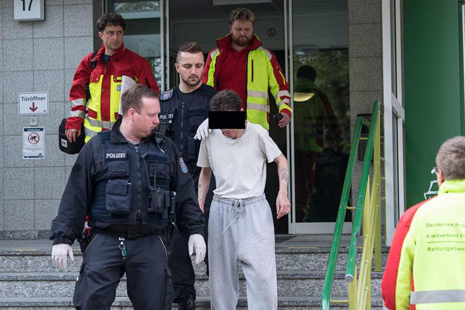 Der psychisch Kranke wurde von Beamten zu einem Rettungswagen gebracht.