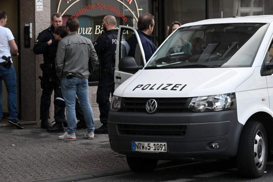 Polizeibeamte stehen vor einem Haus in der Josef-Schregel-Straße, das wegen Terrorverdachts durchsucht wird.
