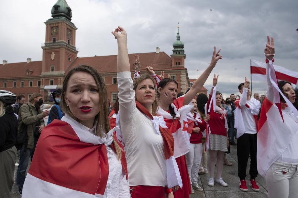 In historische belarussische Nationalfahnen gehüllte Frauen nehmen an einer Demonstration zur Unterstützung der regierungskritischen Proteste in Belarus teil. Die Gewinnerinnen des Preises, die darüber berichtet hatten, sitzen im Knast.