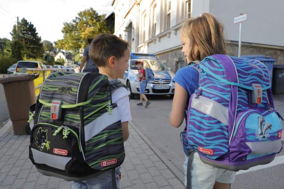 Anton und Paulina Brückom (beide 6) liefen am Montag das erste Mal zur Schule - im Hintergrund passte die Polizei auf.
