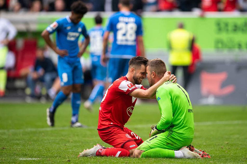 Düsseldorfs Niko Gießelmann (l) und Torwart Michael Rensing jubeln über ihren ersten Saisonsieg, während die Hoffenheimer Reiss Nelson (l.) und Adam Szalai (hinten, Nr. 28) mit hängenden Köpfen den Platz verlassen.