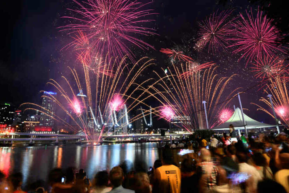 Menschen beobachten ein Feuerwerk in Brisbane.