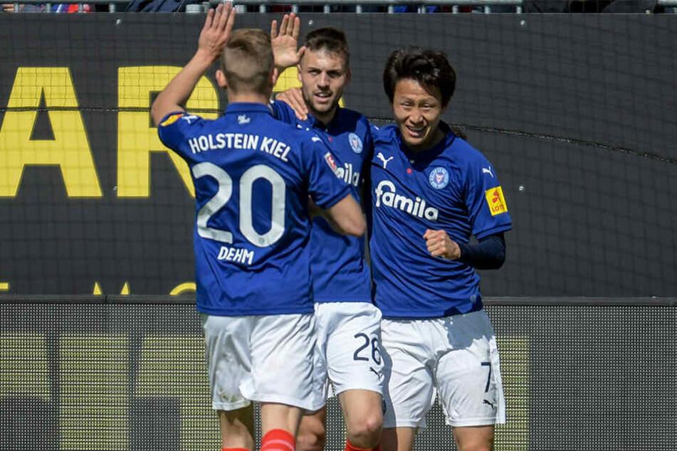 Kiels Jannick Dehm (l-r), Jonas Meffert und Torschütze Jae-Sung Lee feiern den Treffer zum 1:0.