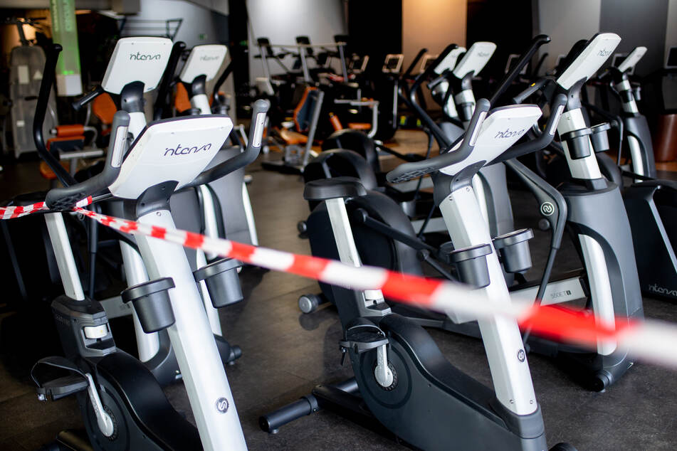 Ein rot-weißes Flatterband ist an Fahrradtrainern befestigt, die in einem Fitnessstudio stehen. Fitnessstudios in Niedersachsen müssen vorerst weiter geschlossen bleiben.