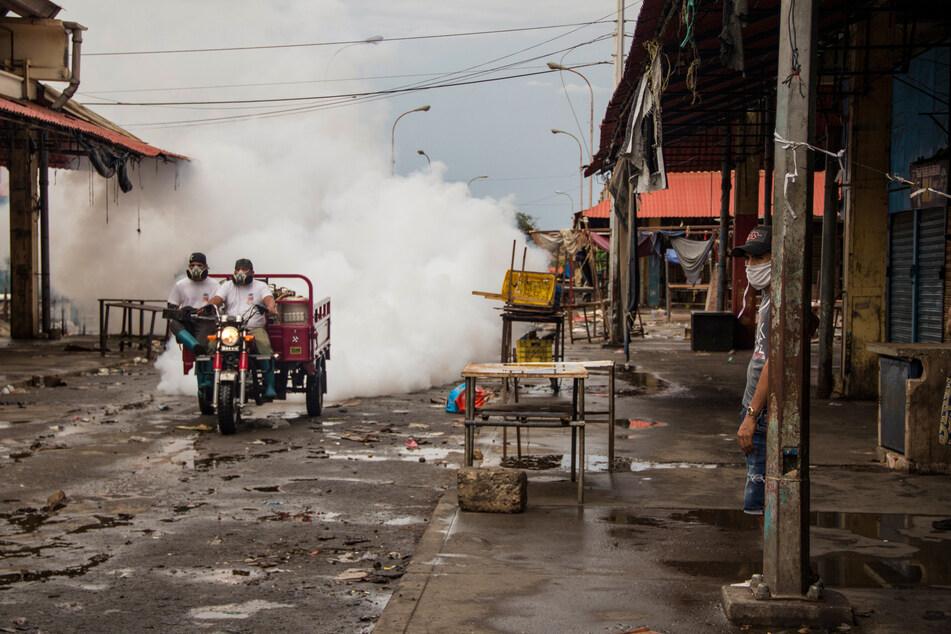 """Zwei Männer mit Mundschutzmasken fahren durch den Markt """"Las Pulgas"""" und sprühen Desinfektionsmittel gegen die Ausbreitung des Coronavirus. Der Markt, der als kritischer Ansteckungsherd galt, wurde am 24. Mai geschlossen. Die venezolanische Regierung hat landesweit 1.245 Covid-19-Infizierte festgestellt. Laut offiziellen Angaben sollen elf Menschen nachweislich an Coronavirus gestorben sein."""