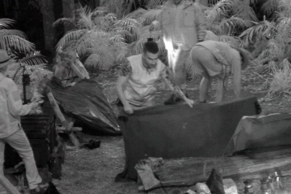 """Regen in der Nacht: Team """"Base Camp"""" bringt schnell die Klamotten in Sicherheit."""