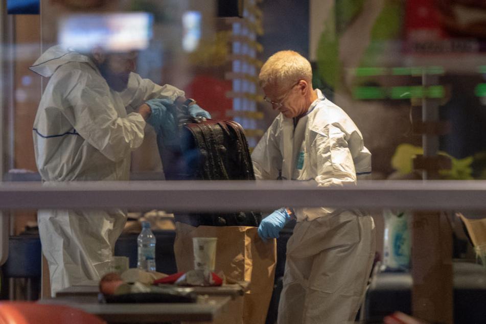 Mitarbeiter der Spurensicherung der Polizei stellen in einer McDonalds-Filiale im Hauptbahnhof einen verkohlten Koffer sicher.