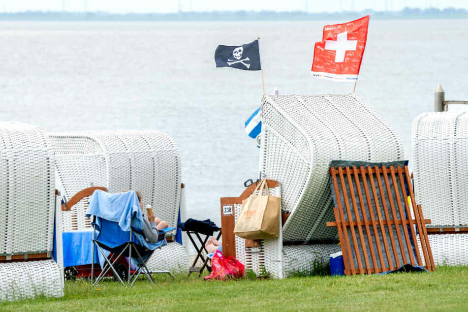 Touristen sitzen in Strandkörben in Wilhelmshaven.