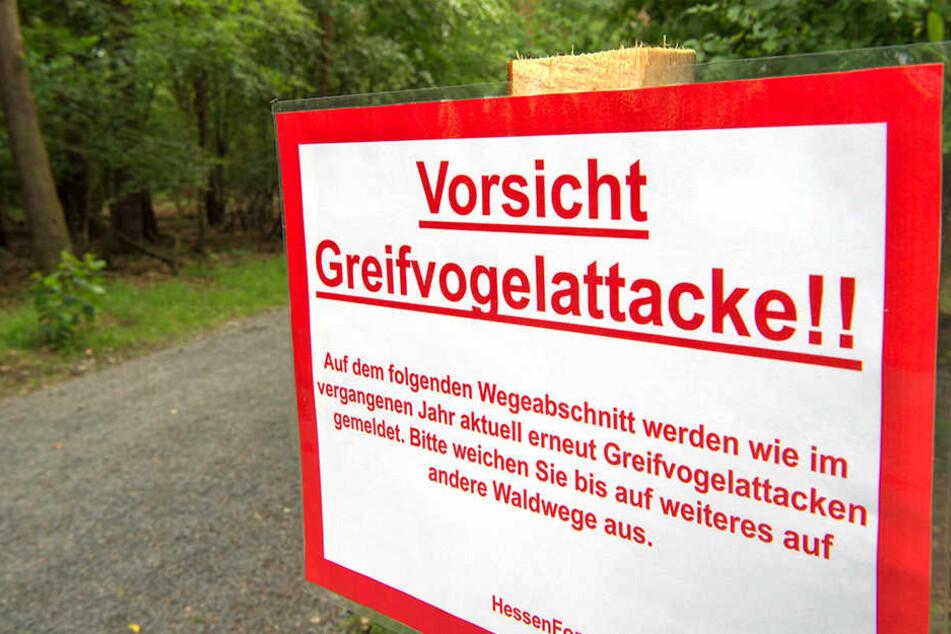 Ein Schild warnt Spaziergänger vor Greifvogelattacken.