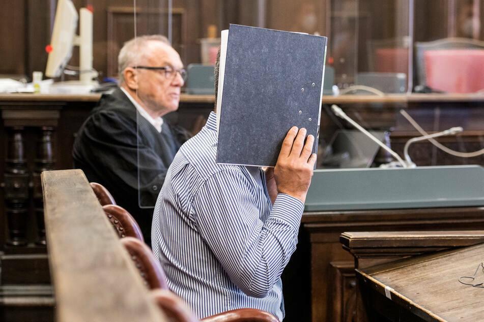 Der Angeklagte (vorne) sitzt im Landgericht im Sitzungssaal neben seinem Verteidiger.
