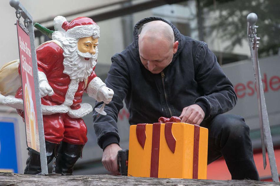 Ein Helfer befestigt an der Münzgasse letzte Deko-Geschenke. Der Markt startet morgen.