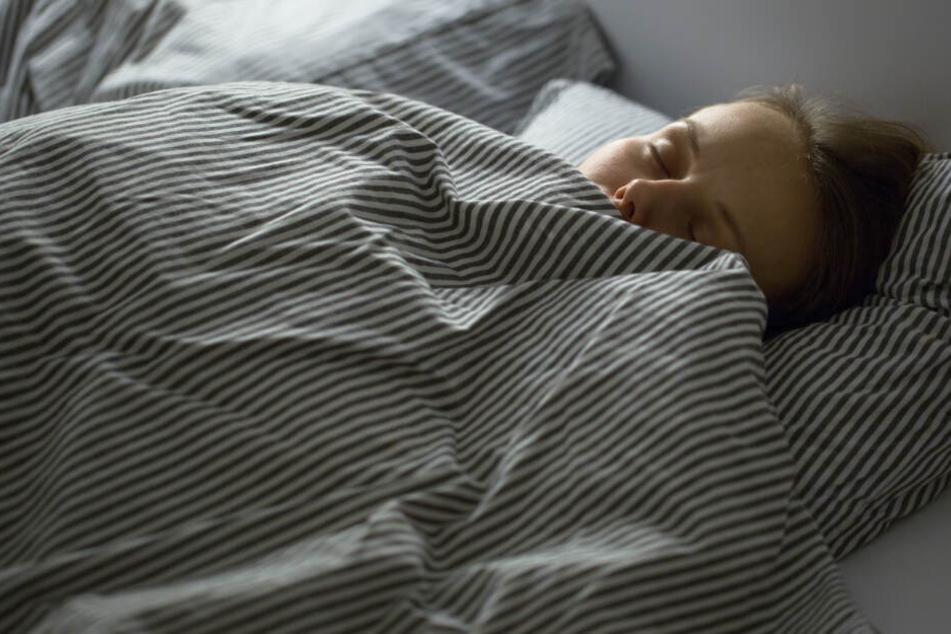 Eine Frau hat es sich in einem fremden Bett bequem gemacht. (Symbolbild)