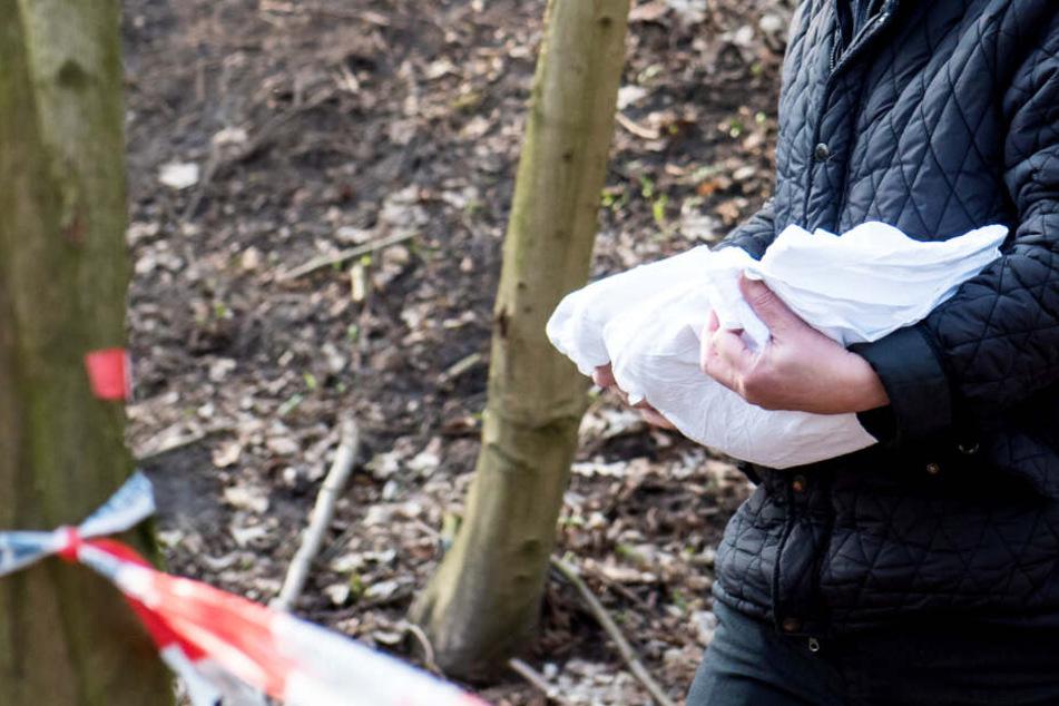 Ein Bestatter trägt das tote Baby vom Fundort weg.