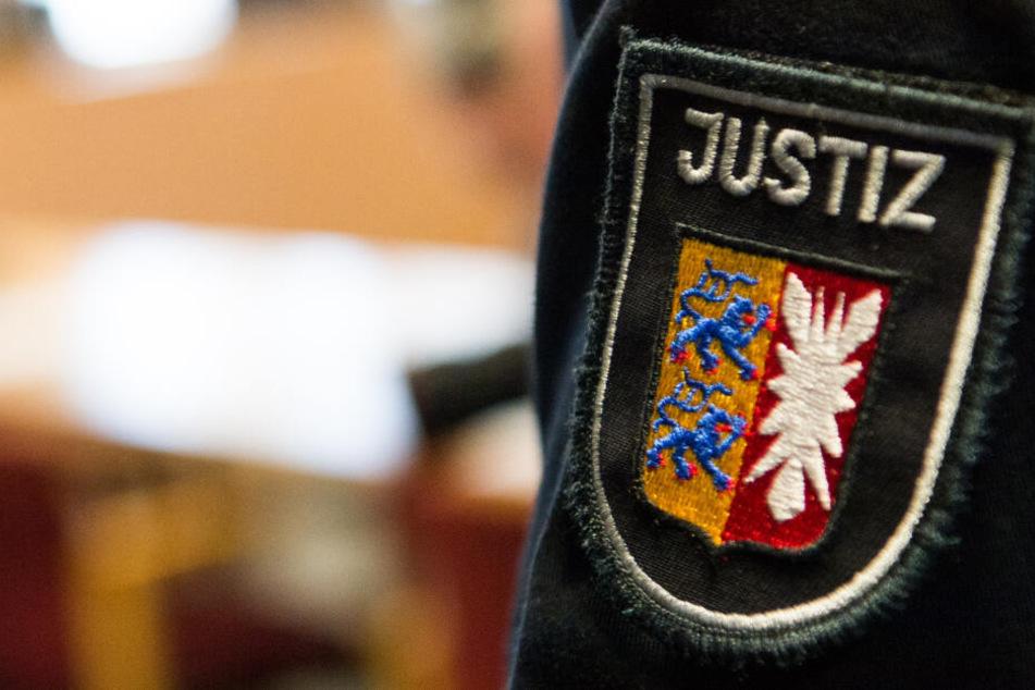 Der Justiz-Aufnäher auf dem Pullover eines Beamten (Symbolbild).