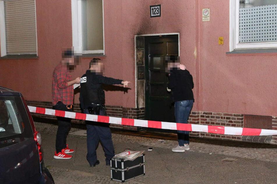 Kriminalpolizisten stehen vor dem Haus.