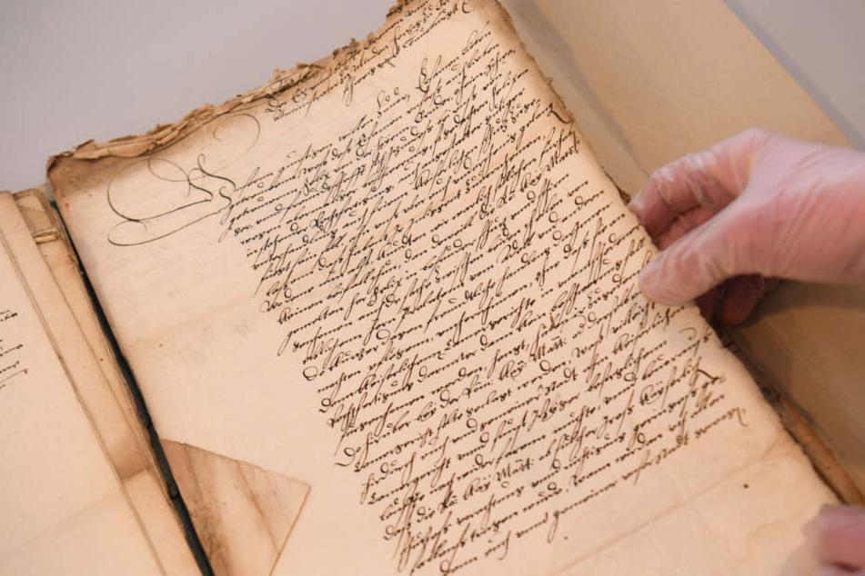 Die Restauratorin zeigt die Original-Akten aus dem Bestand des Stadtarchivs.