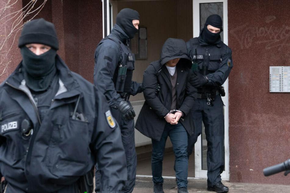 Zwei Polizisten führen in Berlin-Mitte eine tatverdächtige Person ab.