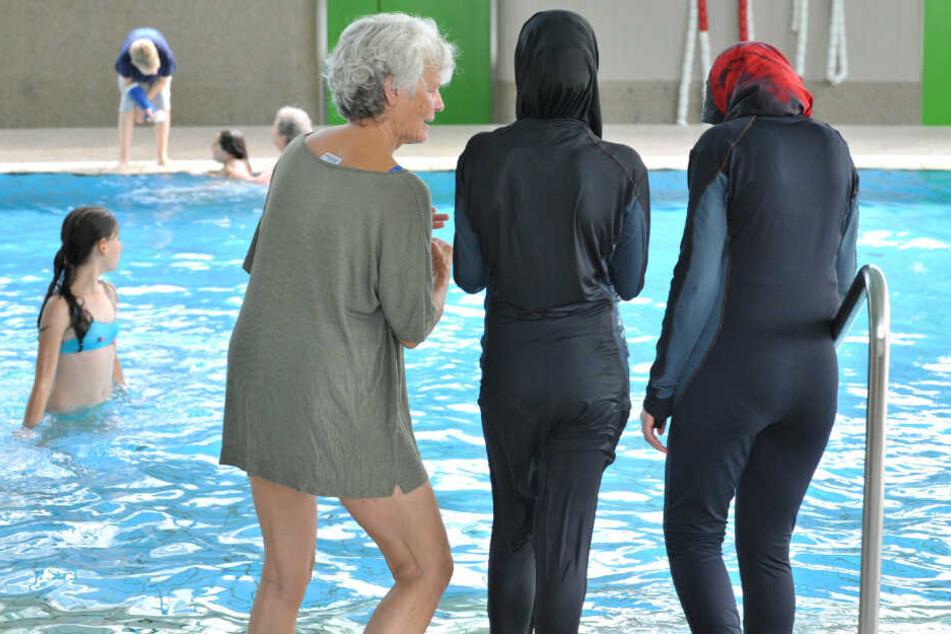Zwei Schülerinnen stehen in ihren Burkinis vor dem Schwimmbecken.