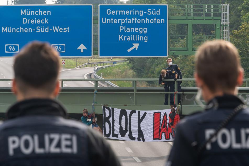 Aktivisten haben sich am Eröffnungstag der IAA Mobility von Autobahnbrücken rund um München abgeseilt und Banner entrollt.