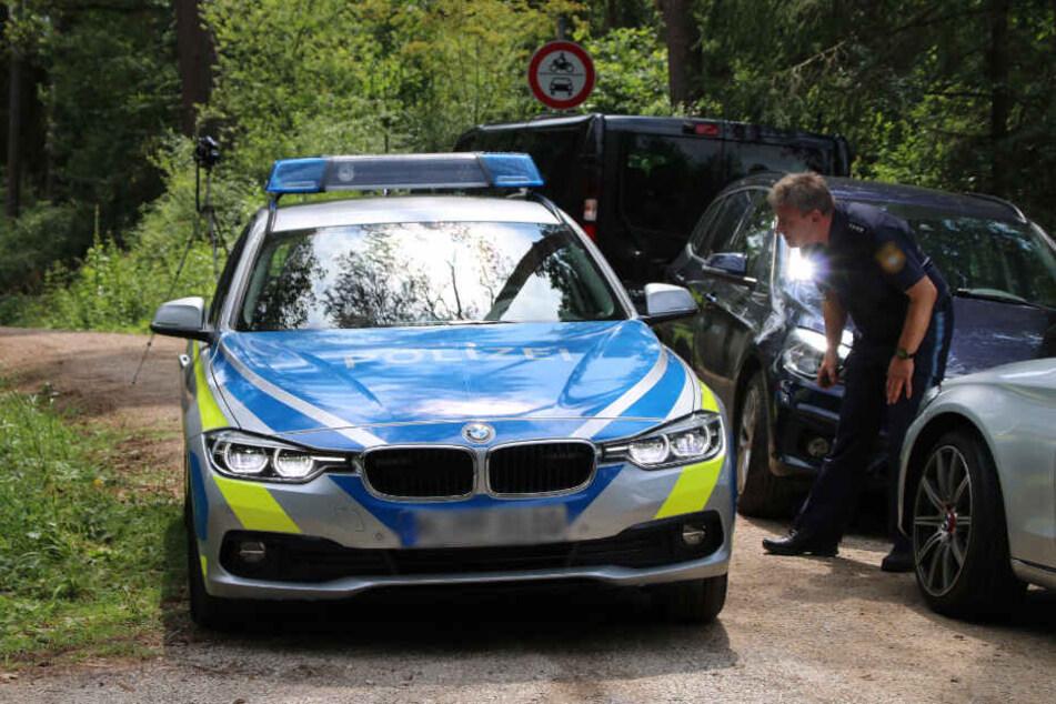 Die Polizei steht nach einem Leichenfund auf einem Waldweg. (Symbolbild)