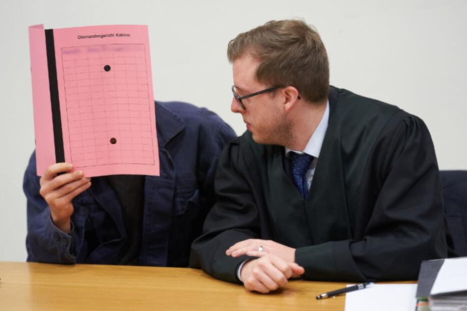 Der Angeklagte sitzt am 28.01.2020 im Gerichtssaal des Oberlandesgerichts Koblenz neben seinem Anwalt Marius Müller (r.).