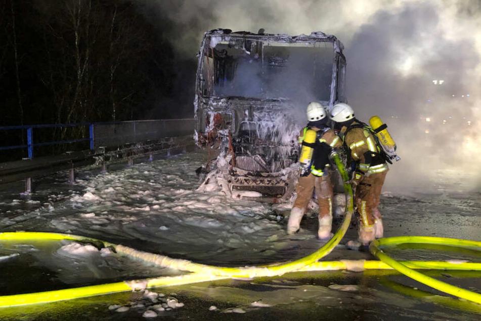 Feuerwehrleute löschen das brennende Führerhaus.
