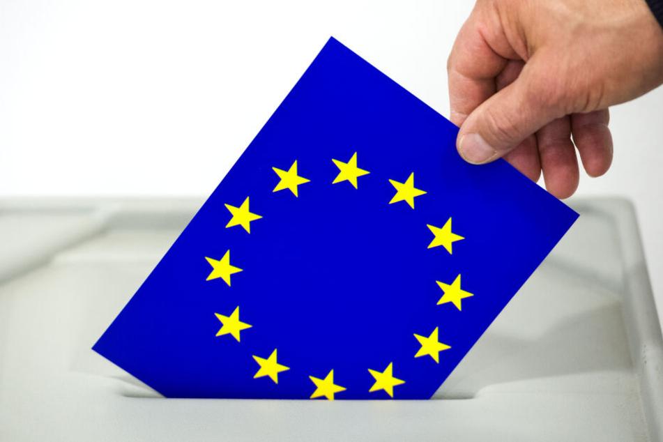 Ein Mann steckt eine Karte mit dem Aufdruck der Europaflagge in den Schlitz einer Wahlurne. In Deutschland findet die Wahl am Sonntag, dem 26. Mai 2019 statt.