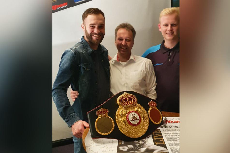 Foto mit Weltmeistergürtel (v.l.): Dominic Bösel (30), Sven Meyer (44) und Dart-Spieler Sven Hesse (19).