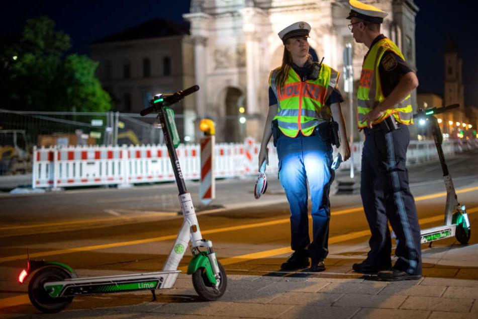Polizisten stehen bei einer E-Tretroller-Kontrolle in München.