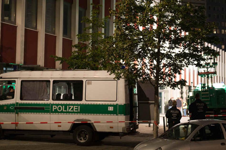 Einsatzfahrzeuge der Polizei stehen in Berlin im Stadtteil Mitte am Abend vor einer Absperrung.