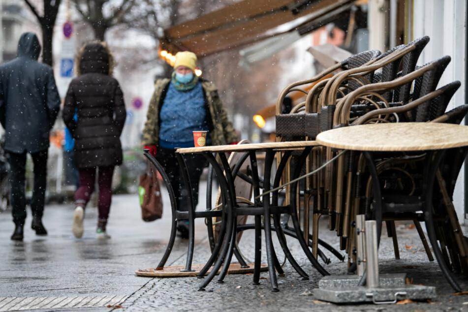 Ein Kaffeebecher aus Pappe steht auf einem Tisch vor einem geschlossenen Café in Kreuzberg.