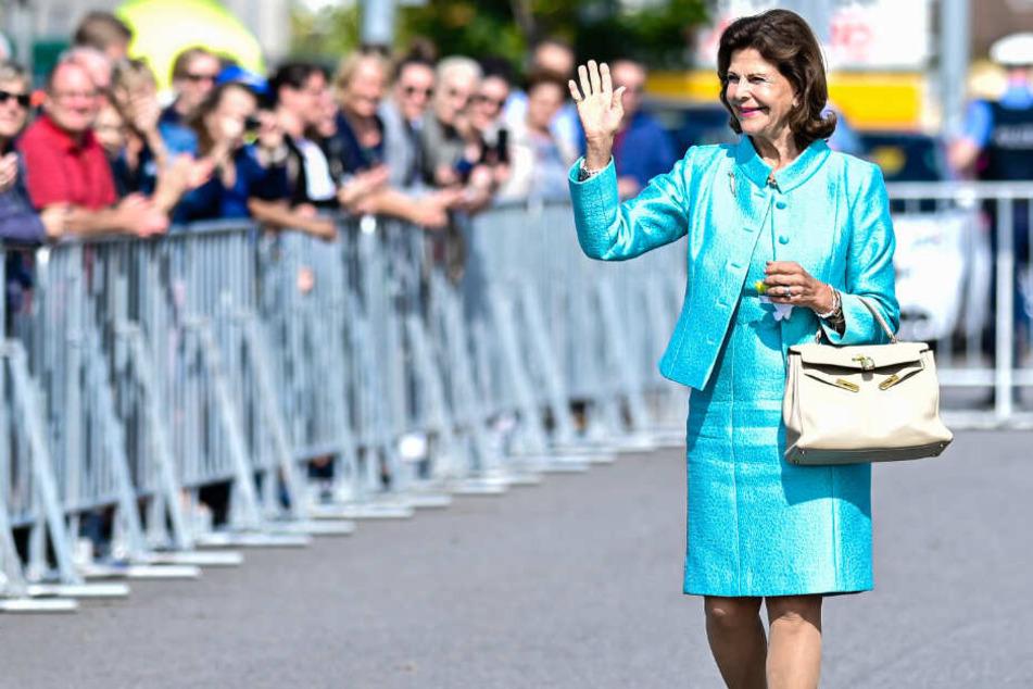 Königin Silvia winkt der Menge bei einem Besuch in Bensheim (Hessen) zu,