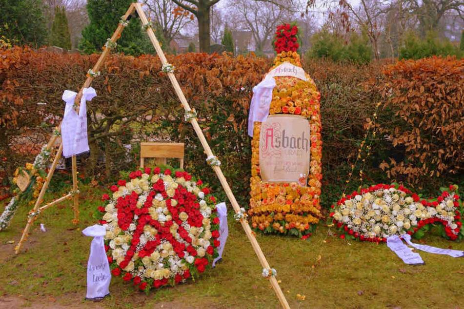 Neben dem Grab steht eine zwei Meter hohe Asbach-Uralt-Flasche aus Blumen.
