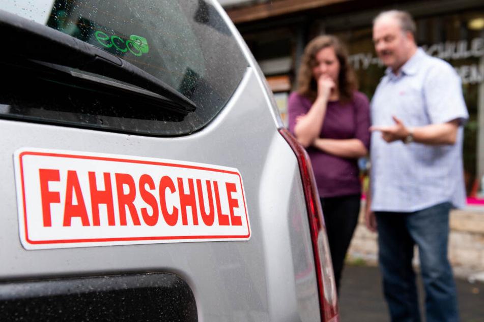 Ein Fahrlehrer erläutert einer Schülerin vor der Fahrt am Auto technische Details. Der Praxis-Teil liegt den Sachsen besser als die Theorie.