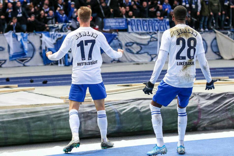 Maximilian Mittelstädt (l) feiert mit Dodi Lukebakio den Treffer zum 1:0 vor der Ostkurve.
