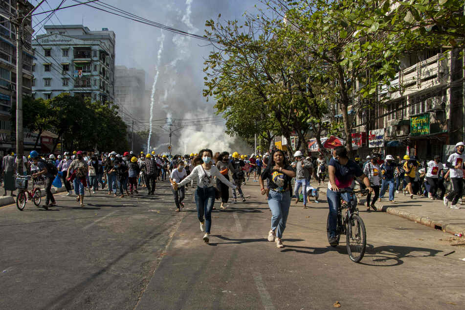 Anti military coup protesters run in the middle of tear gas smoke during a demonstration against the military coup.