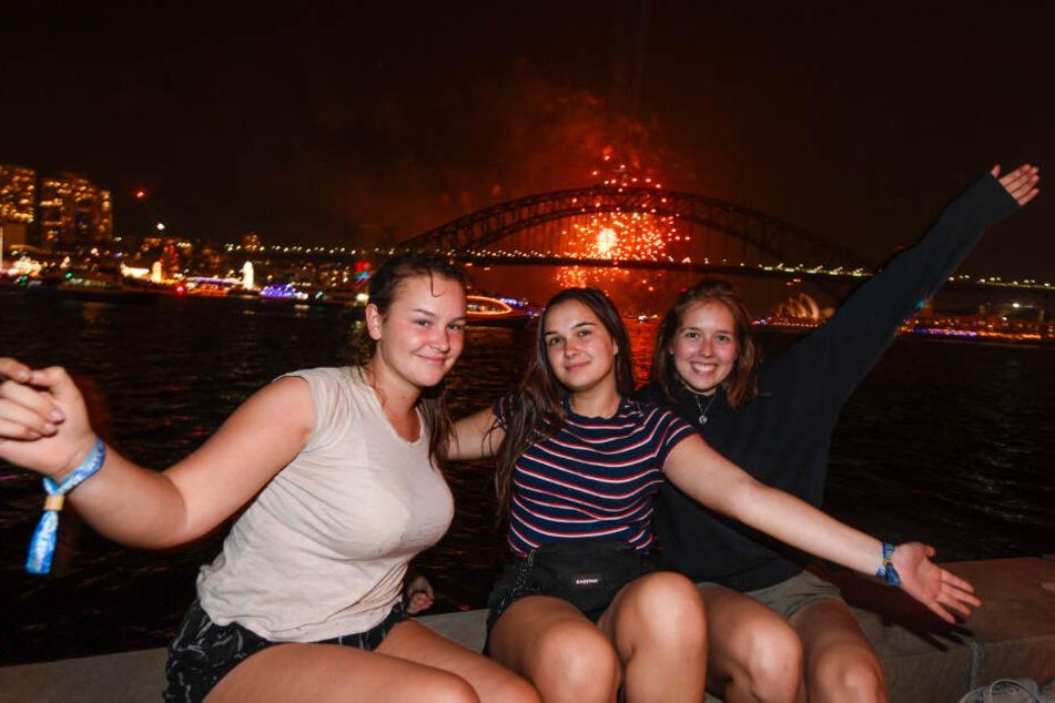 """Die Touristinnen Paula Nobbe (l-r), Alina Wegmann und Finja Kirchhoff aus Deutschland sitzen für ein Foto während des Familien-Feuerwerks """"The 9pm Family Fireworks"""" im Hafen zusammen."""