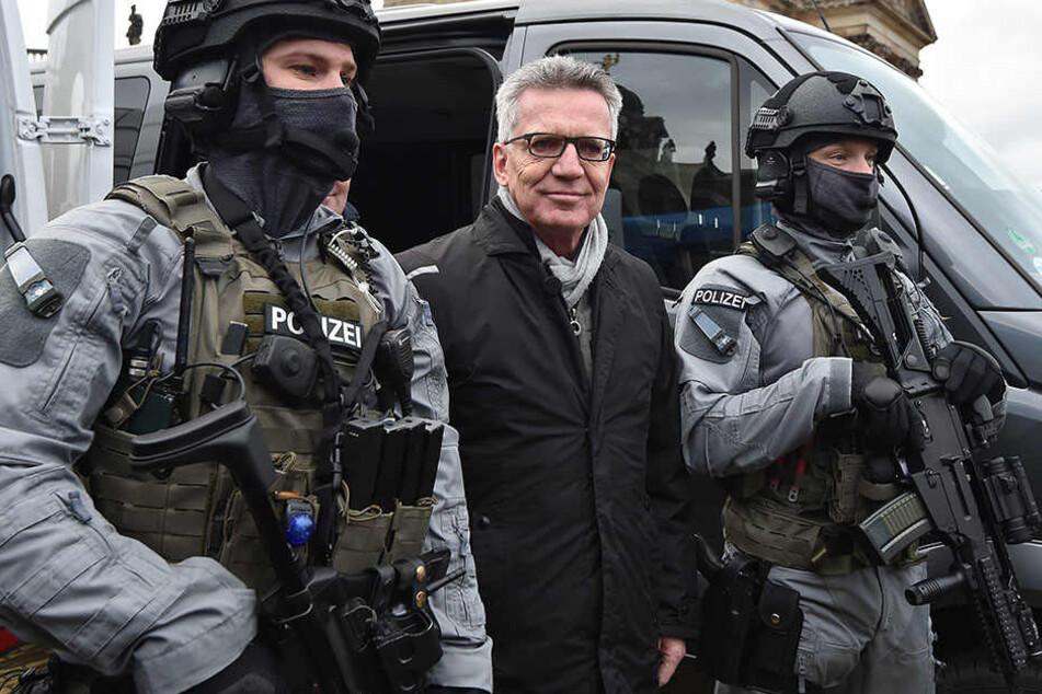 Bundesinnenminister Thomas de Maiziére zwischen schwer bewaffneten Polizisten in Potsdam.