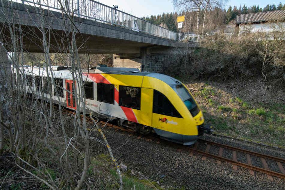 Ein Zug der Hessischen Landesbahn fährt unter einer Brücke durch. Mehrere Gullydeckel waren auf Höhe der Fahrerkabine an Seilen von der Brücke festgebunden.
