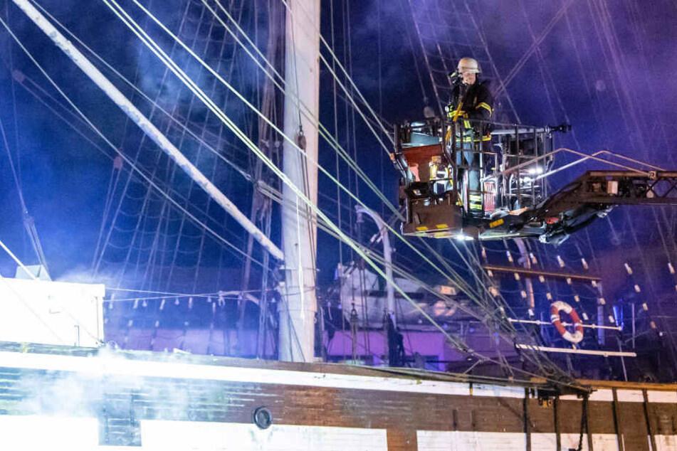 Ein Feuerwehrmann ist auf dem Leiterwagen im Einsatz, um den Brand auf dem Schiff zu löschen.