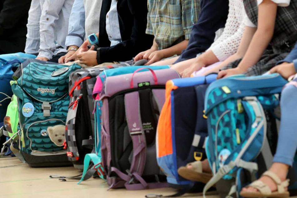 Grundschüler warten auf einer Bank. (Symbolbild)