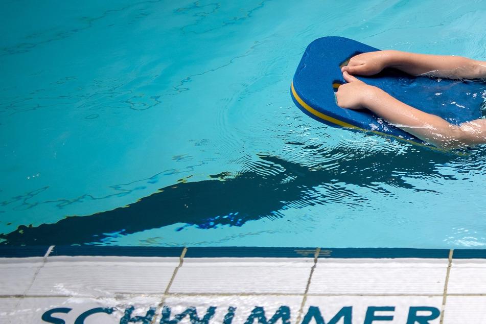 Ein Schüler schwimmt mit einer Schwimmhilfe durch ein Schwimmbecken. Nach der Corona-Pandemie soll Sport und Bewegung an Kitas und Schulen stärker gefördert werden.
