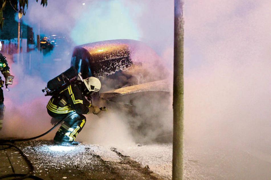 Feuerwehrleute löschen in Leipzig-Leutzsch einen brennenden Dienstwagen der Deutschen Bahn.