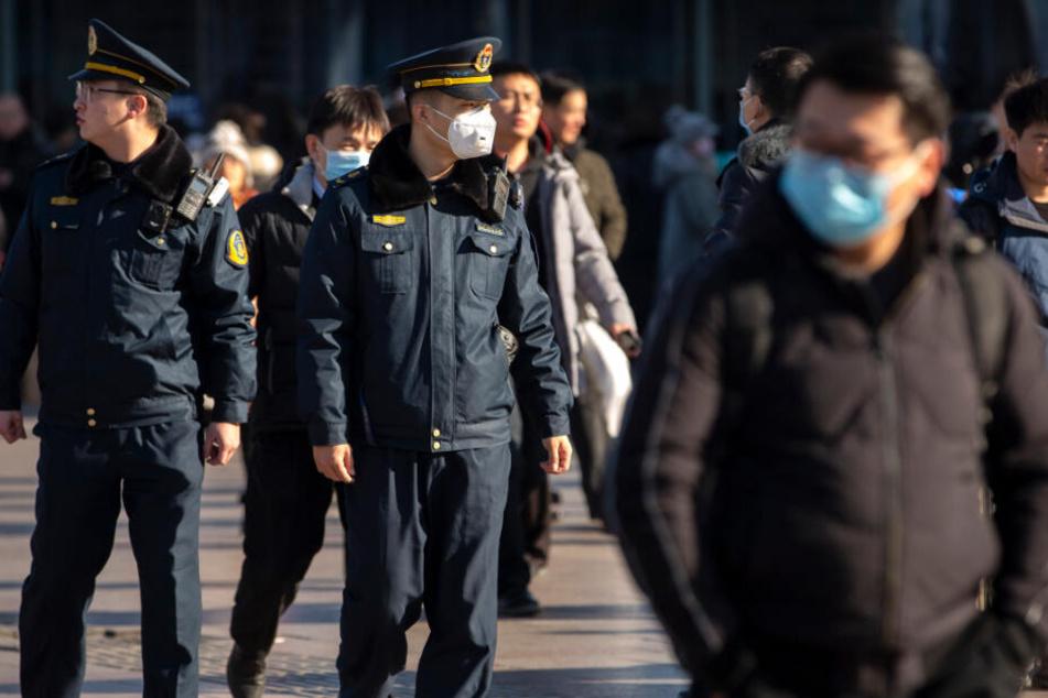 Viele Menschen in China schützen sich mit einem Mundschutz (Symbolbild).