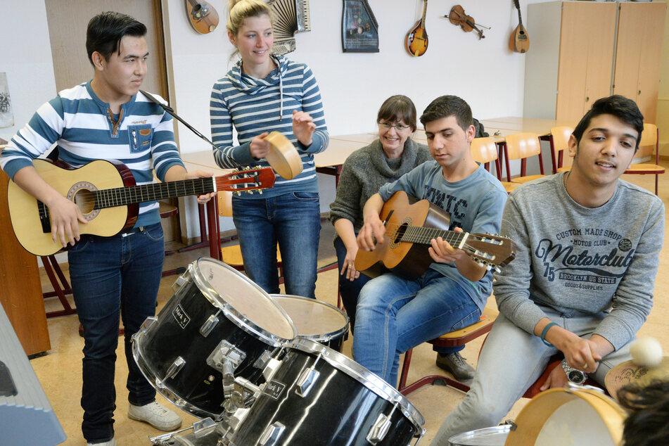 Afghane Khaled (15, l.), Lehrerin Lisa Berger, Schulleiterin Elke Fischer, Syrer Mohamad (18) und Serbe Stefan (15) bei einem Musikprojekt in der Oberschule Paunsdorf in Leipzig.